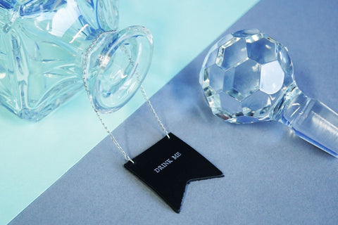 Custom decanter tags made from black leather and embossed with silver foil. This tag has the phrase Drink me