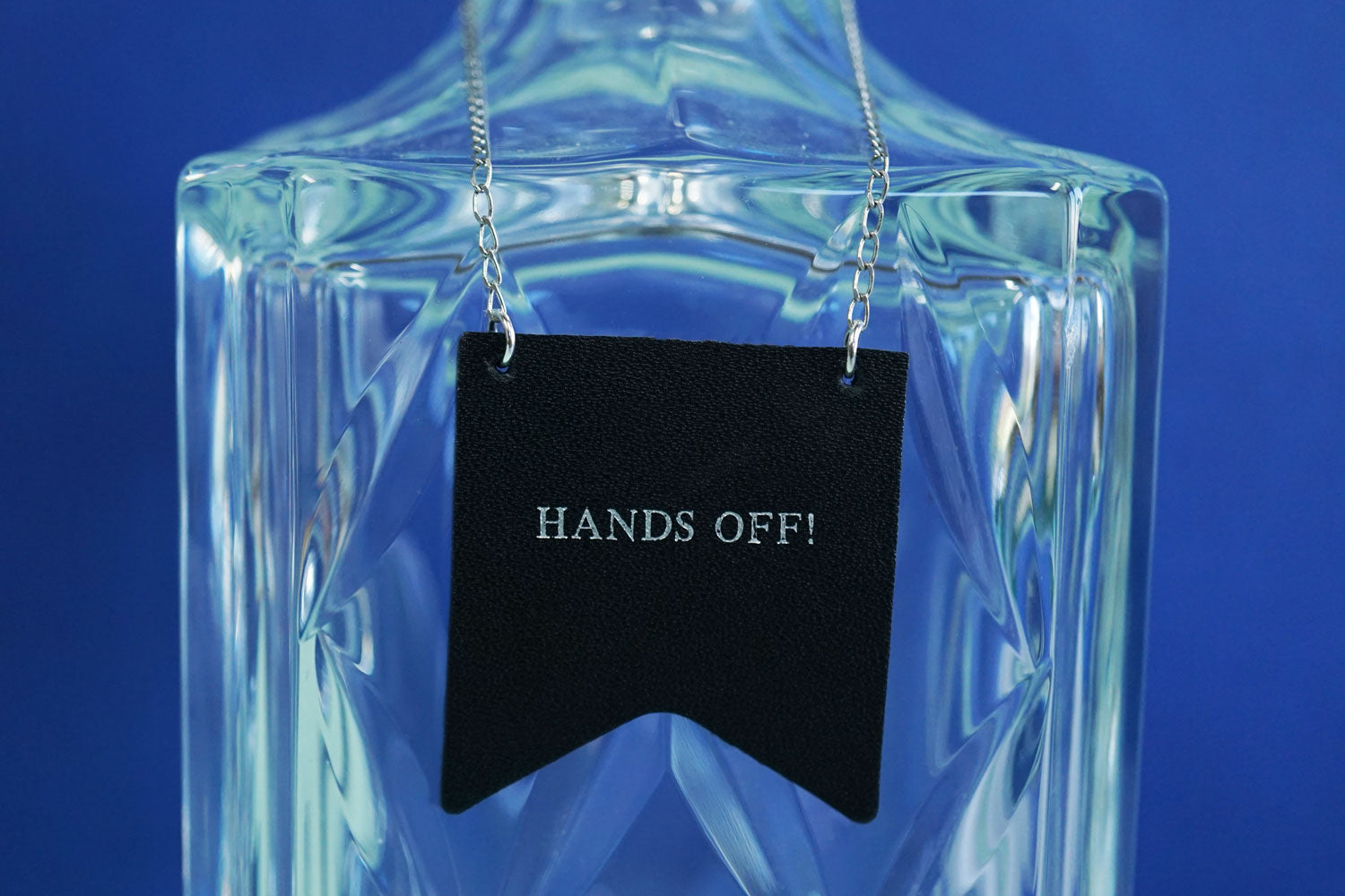 Custom decanter tags from Bookshell Bindery embossed in silver foil with the phrase Hands off!