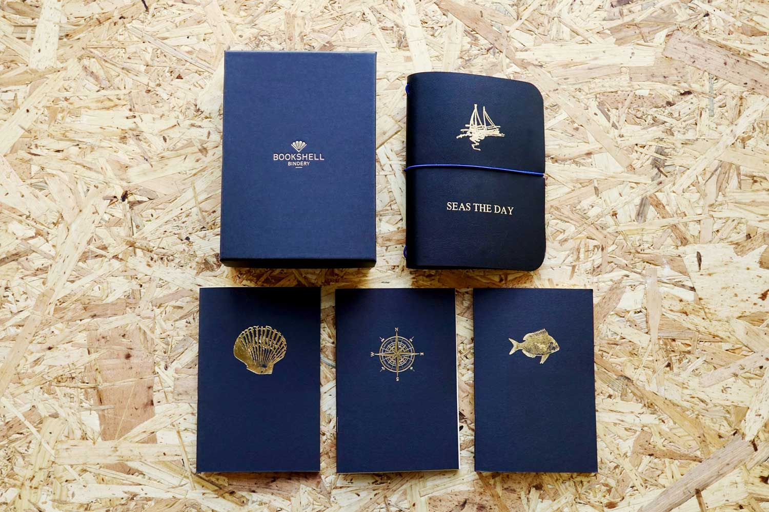 Never-ending journal - Seas the day, leather travel journal, A6 pocket size with boat illustration embossed in gold foil onto the cover, this photo shows all 3 inner notebooks with a shell, fish and compass illustration on the covers