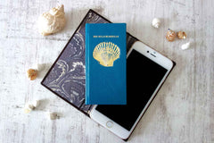 Leather iphone case from Bookshell in blue leather with shell cover picture embossed in gold foil and title She sells sea shells