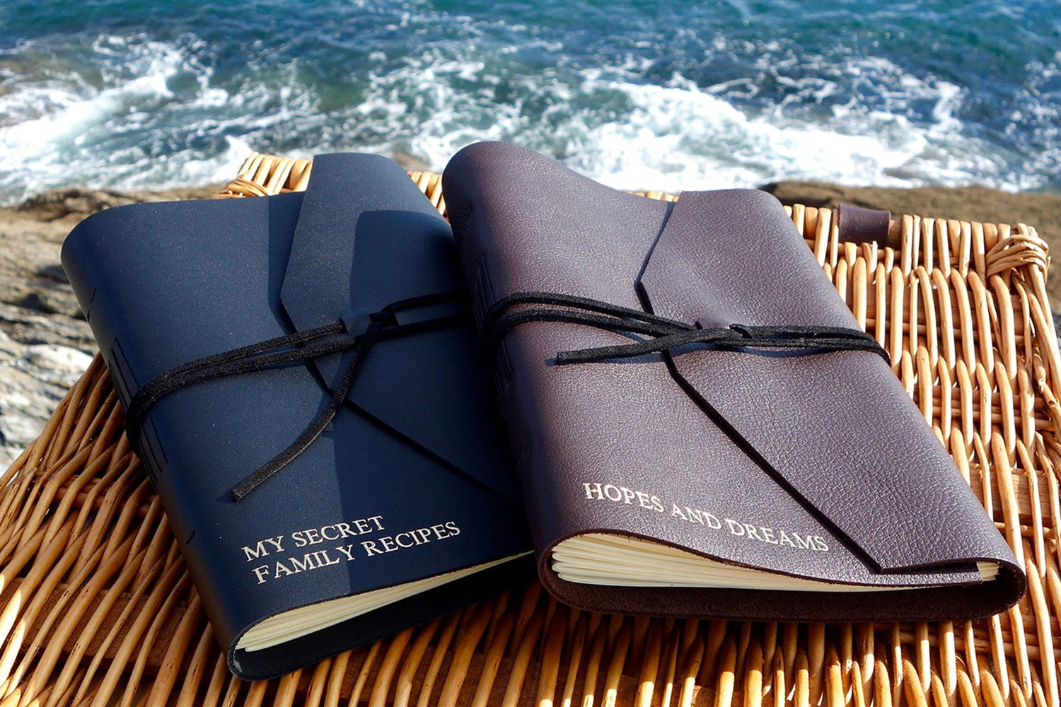 Two leather journals on a picnic hamper by the sea, personalised with My secret family recipes and Hopes and dreams