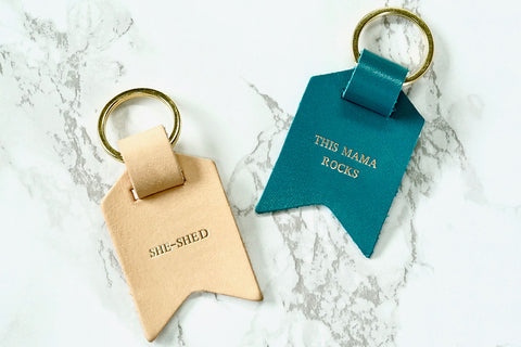 Mum keychain from Bookshell Bindery embossed with gold foil, she-shed and This mama rocks, in pale pink and turquoise blue leather