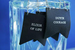 Personalised bottle label from Bookshell Bindery, 3 labels hanging on a glass decanter, embossed with the text Elixir of life and Dutch courage