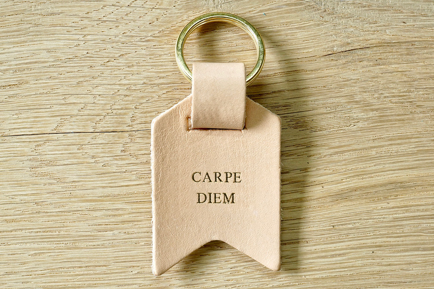 Peronalised keyrings from Bookshell Bindery in natural pale pink leather embossed with gold foil, Carpe Diem
