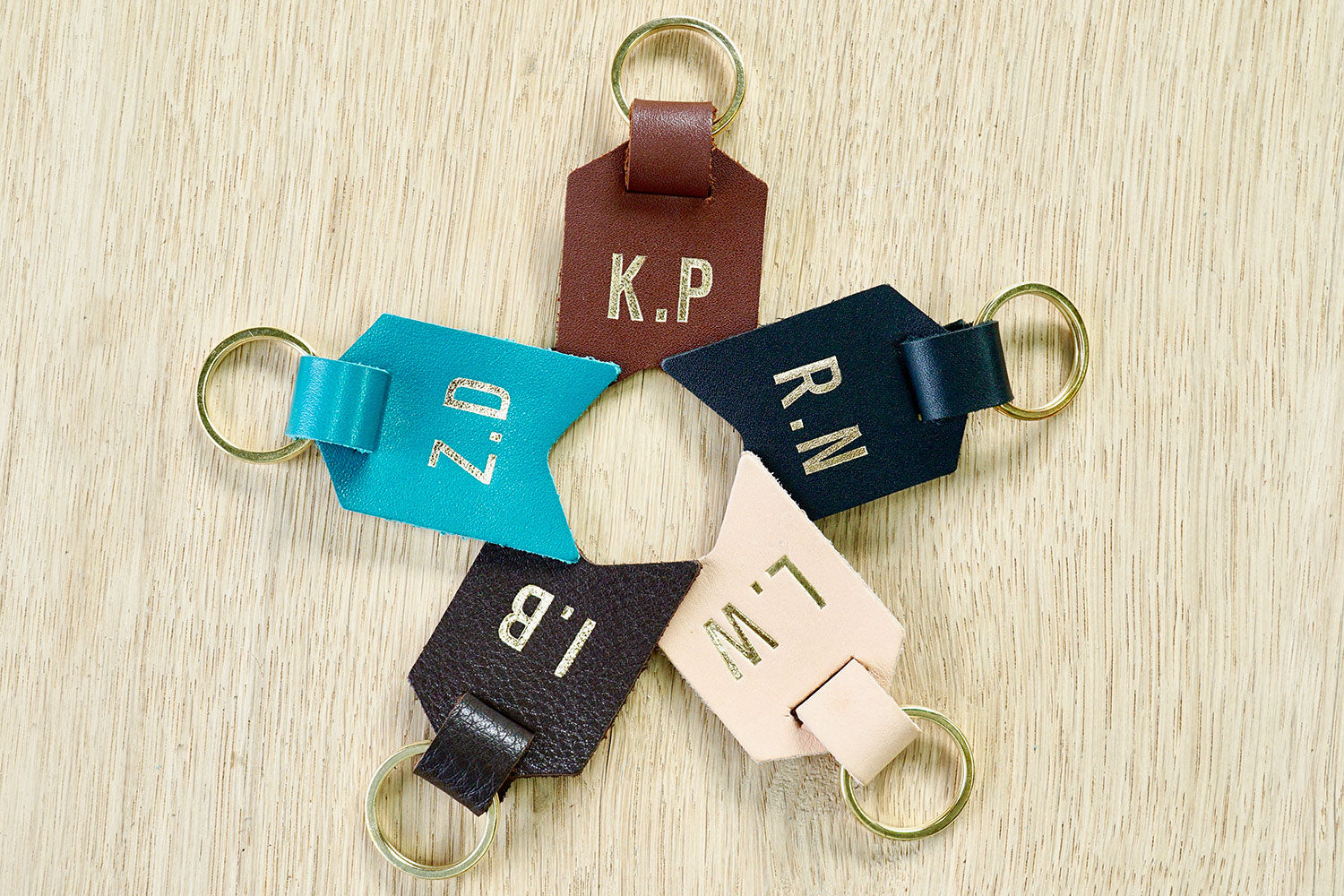 Peronalised keyrings from Bookshell bindery available in black leather, turquoise blue leather, dark brown leather, light brown leather, Natural (pale pink)