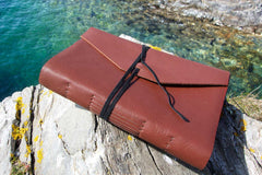 Personalized leather journal in light brown leather from Bookshell bindery with Travel journal embossed in gold on the cover
