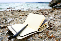 Black Vegan Leather Journal made from Pinatex Pineapple leather from Bookshell Bindery shown here in the beach