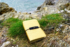 This is our gold textured Vegan Leather Journal photographed here at the edge of a cliff