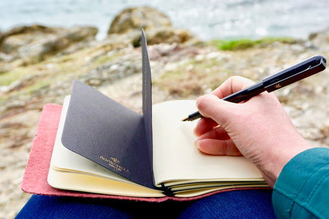 Pink Vegan Leather Journal made from Pinatex Pineapple leather from Bookshell Bindery photographed in use on the beach