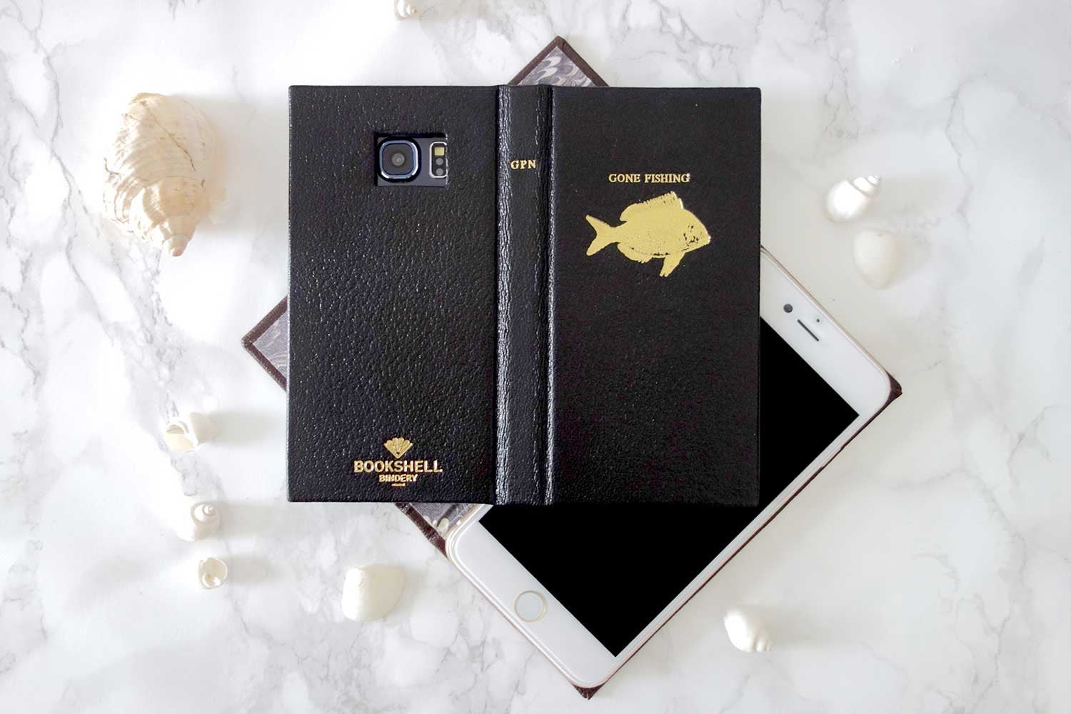 Book phone case with a fish on the cover in black leather from Bookshell Bindery