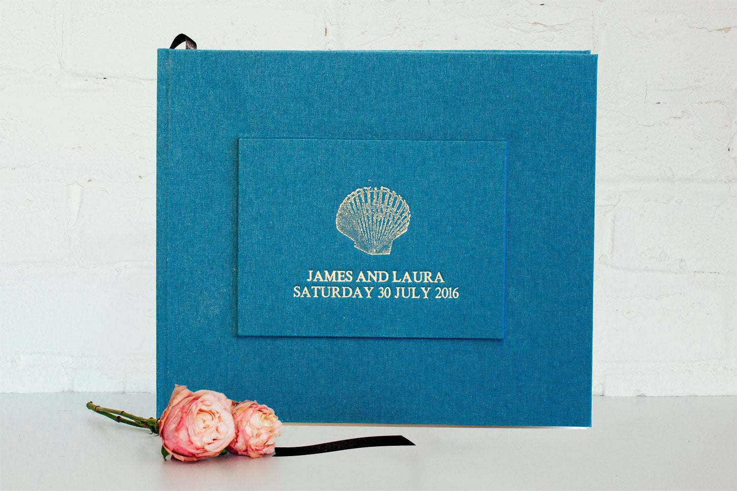 personalised wedding guest book from Bookshell bindery, hand bound in blue book cloth with gold foil embossing, shell cover picture