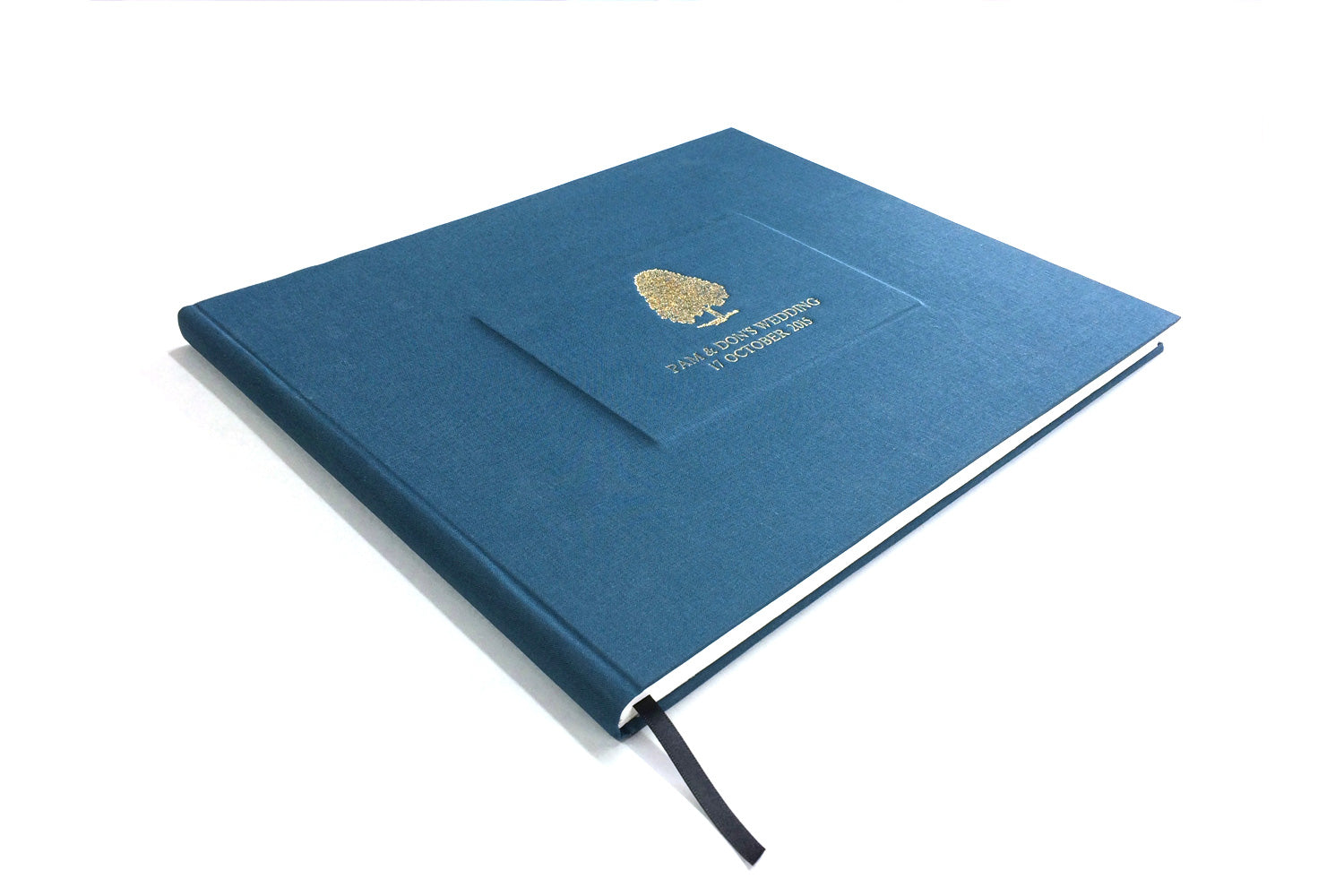personalised wedding guest book from Bookshell bindery, hand bound in blue book cloth with gold foil embossing, tree cover picture