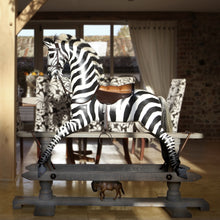 Load image into Gallery viewer, Rocking Zebra in a home with a dining table in the background mounted on a safety stand with no saddle blanket
