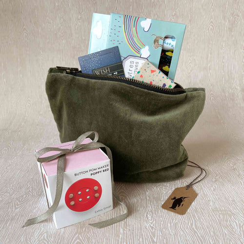budding-artist-gift-set-showing-a-moss-green-velvet-pouch-holding-thoughtfulls-cards-magic-markers-block-crayons-and-sitting-next-to-a-red-button-pom-maker