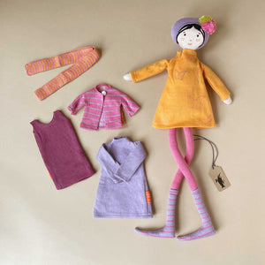 fantine-doll-in-orange-dress-and-purple-hat-with-second-outfit-of-purple-dress-pink-striped-sweater-and-orange-and-pink-leggings