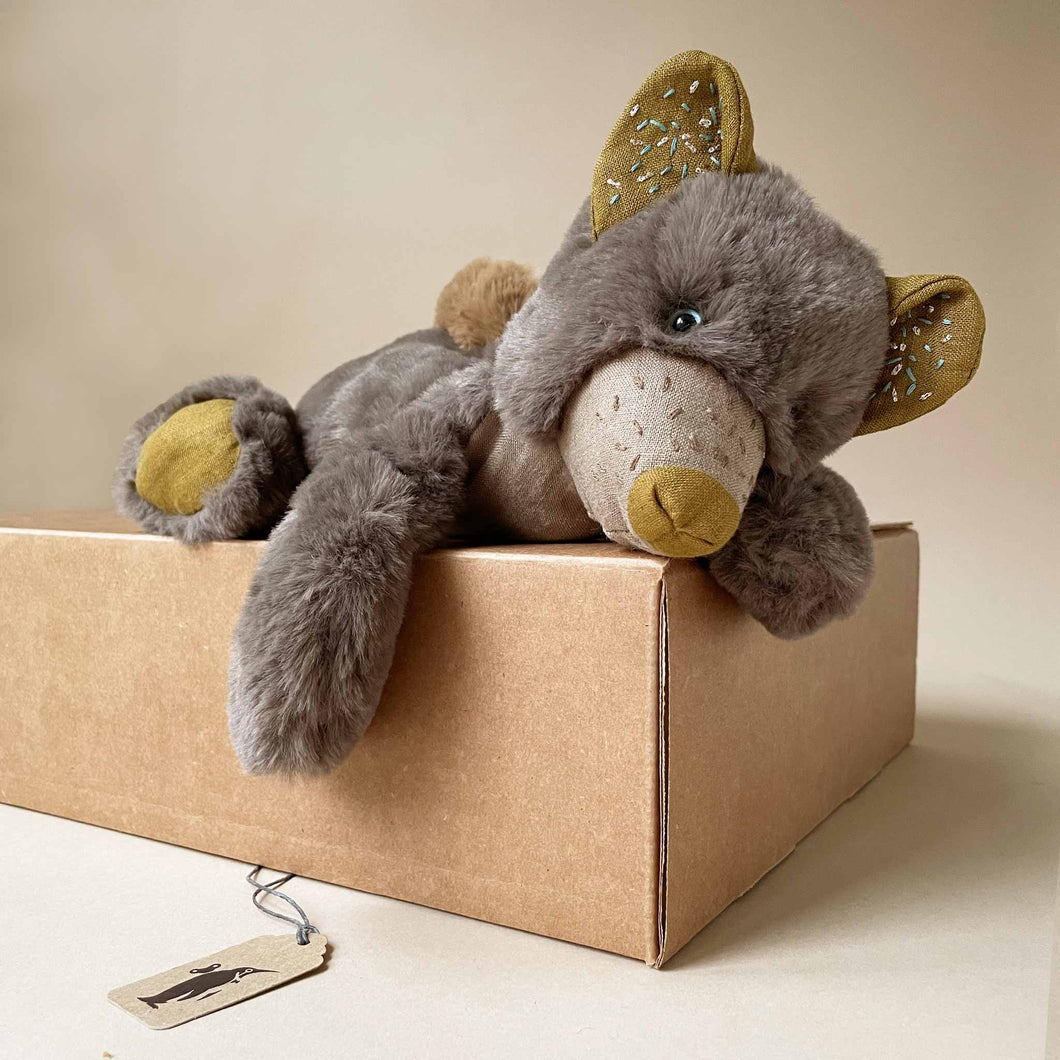 little-pollen-bear-stuffed-animal-laying-on-gift-box