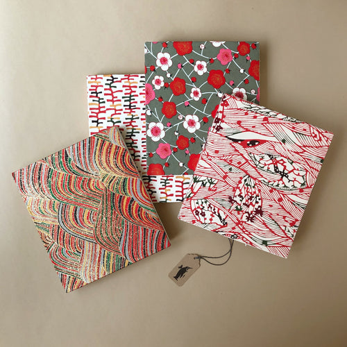 four-hand-bound-notebooks-in-red-tones-ladders-waves-rolling-hill-and-plium-tree-flowers