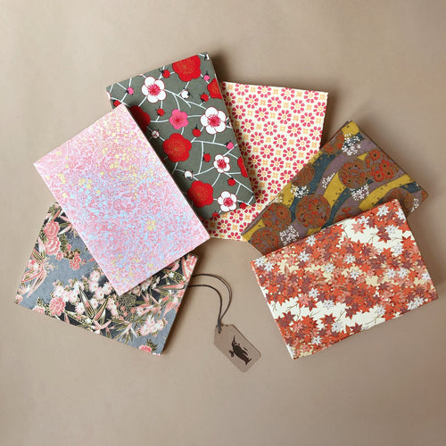 six-petite-hand-bound-notebooks-in-pink-tones-balloons-golden-pink-rose-bamboo-daisies-plum-tree-flowers-and-golden-maple