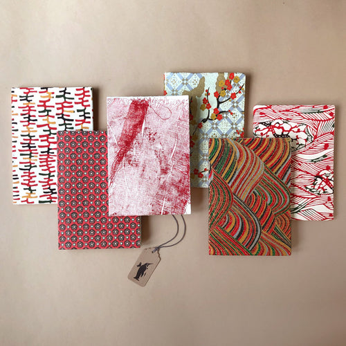 six-petite-hand-bound-notebooks-in-red-tones-ladders-tarlatan-rolling-hills-flower-dot-waves-and-golden-blossoms