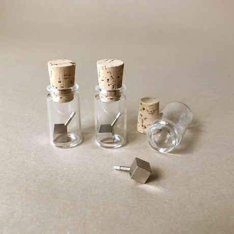 metal-cube-tops-in-glass-jar-with-cork-stopper