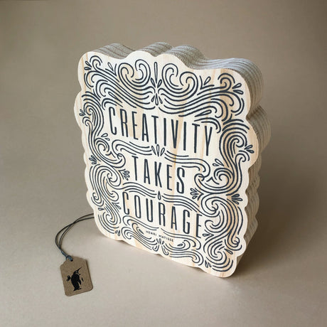 wood-block-art-creativity-takes-courage-ornate-frame-shape-with-black-design-and-text