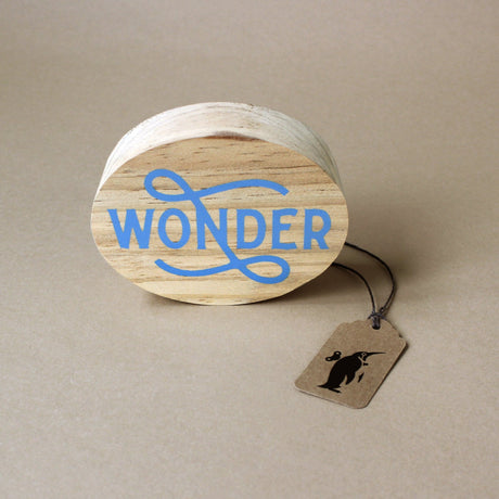 round-wood-block-with-the-word-wonder-printed-in-blue-script
