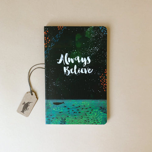 soft-cover-journal-with-the-words-always-believe-and-a-background-of-dark-sky-and-ocean-with-fish