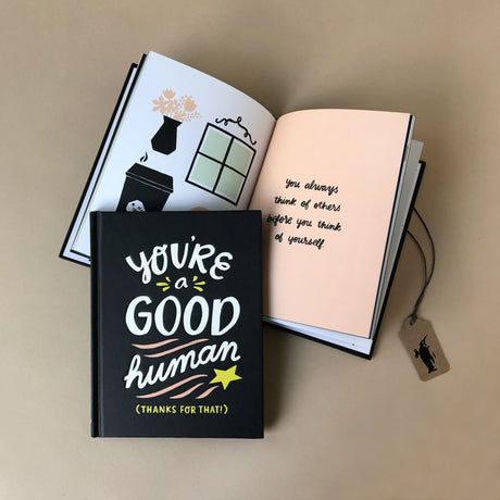 youre-a-good-human-book-black-cover-and-inside-pages-showing-illustrations-of-home-goods-and-text-saying-how-you-always-think-of-others
