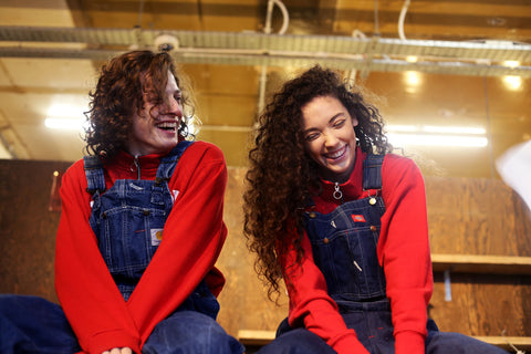 Two laughing people wearing vintage dungarees