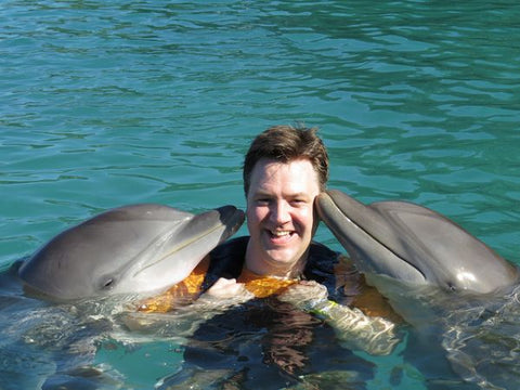 Friendly dolphins kiss man