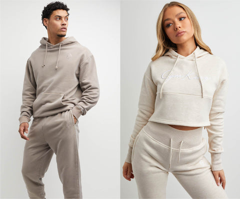 Mens mocha oversized hood and jogger next to women's oatmeal beige two piece tracksuit, crop hood and jogger