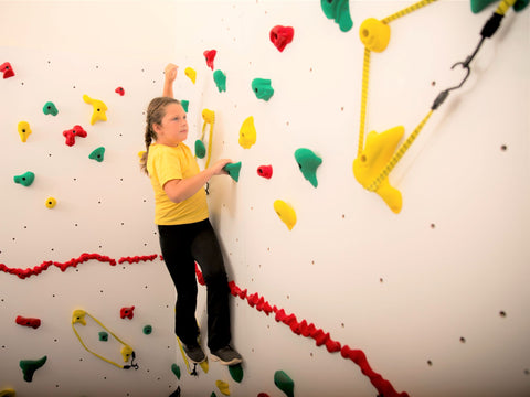 Girl rock climbing avoiding challenges