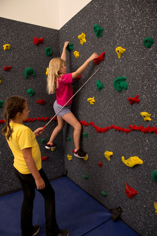 Girl rock climbing while partner points out the next hand hold she should use.