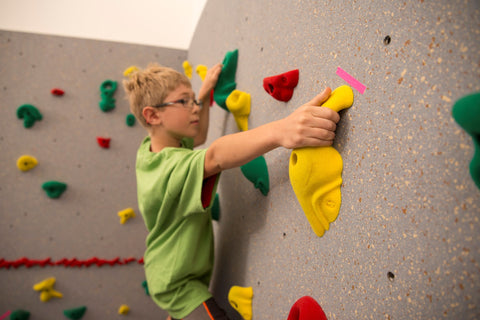 Boy rock climbing in a bouldering event
