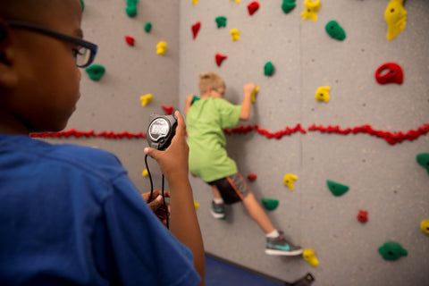 Boy being timed while rock climbing in a speed climbing event