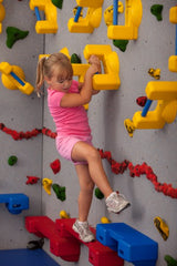 Girl rock climbing using grab-bar style hand holds and ledge-style foot holds