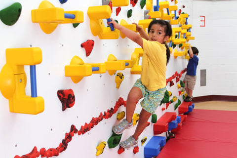 Children climbing on an Adaptive Climbing Wall by Everlast Climbing