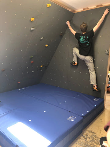 DIY home bouldering wall with boy climbing