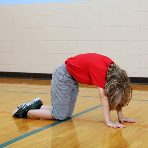 Boy doing cat pose in yoga to be a better rock climber