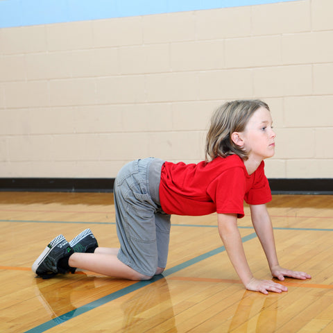 Boy doing cow pose in yoga to be a better rock climber