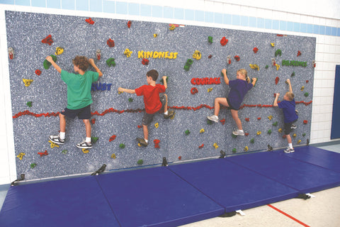 Rock climbers on Traverse Wall with hand holds that spell out positive character traits.