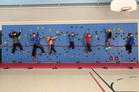 Children rock climbing on a Chroma Wall from Everlast Climbing