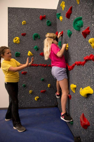 Girl climbing on a climbing wall while blindfolded.