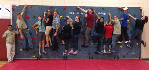 Everlast Climbing employees on a climbing wall they installed for their Day of Caring Program