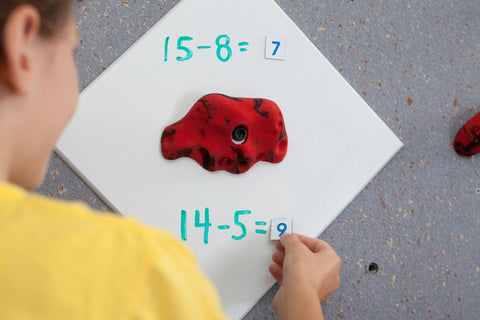 Girl placing magnets on a Discovery Plate while rock climbing