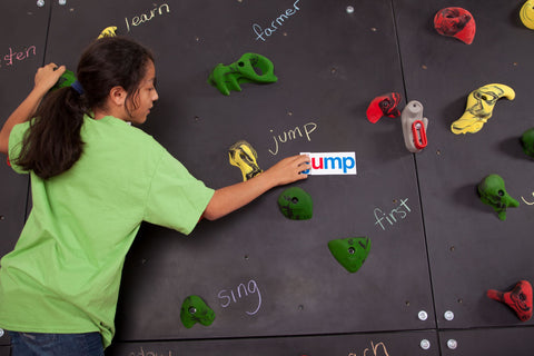 Girl rock climbing and spelling words on a Discovery Blackboard Climbing Wall by Everlast Climbing