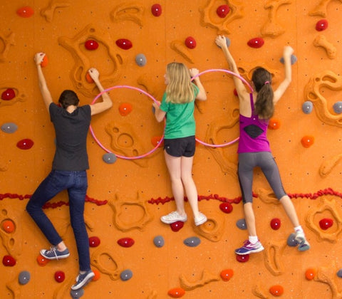 Three girls rock climbing with arms linked with plastic hoops.