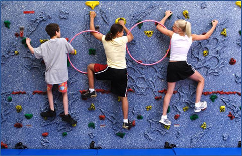 Three children rock climbing with arms linked by hula hoops