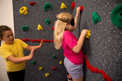 Girl rock climbing blindfolded with responsible partner helping her