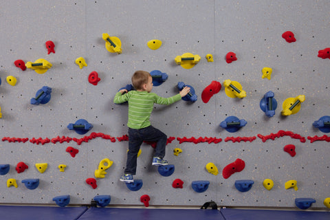 Young boy responsibly rock climbing on a Traverse Wall